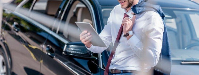 Sælger der sidder på sin bil og kigger på en tablet